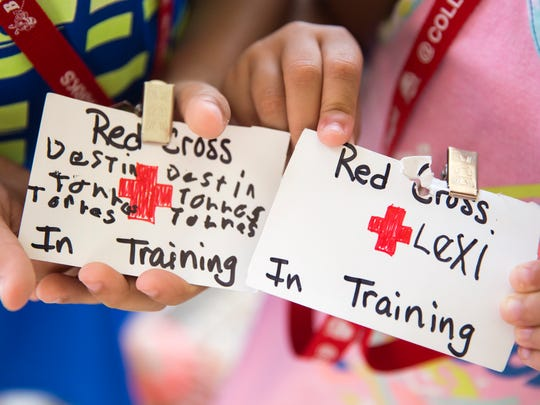 7-year-old Destin, right, and his sister, 6-year-old Lexiann show off the badges made for them by workers at the American Red Cross shelter in the North Collier Regional Park building on Wednesday, September 20, 2017.