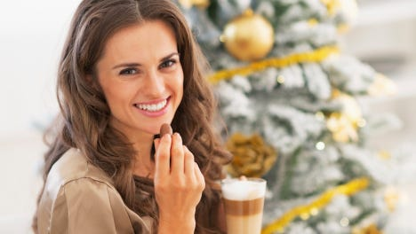 Happy young woman eating candy with latte near christmas tree