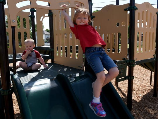 Siblings Easton and Lela play together on the new playground
