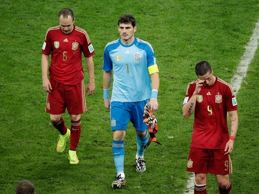 Spain's Andres Iniesta, goalkeeper Iker Casillas and Fernando Torres, from left, leave the pitch after the group B World Cup soccer match between Spain and Chile at the Maracana Stadium in Rio de Janeiro, Brazil, Wednesday, June 18, 2014.  Spain was eliminated from World Cup contention with a 2-0 loss to Chile.  (AP Photo/Christophe Ena)