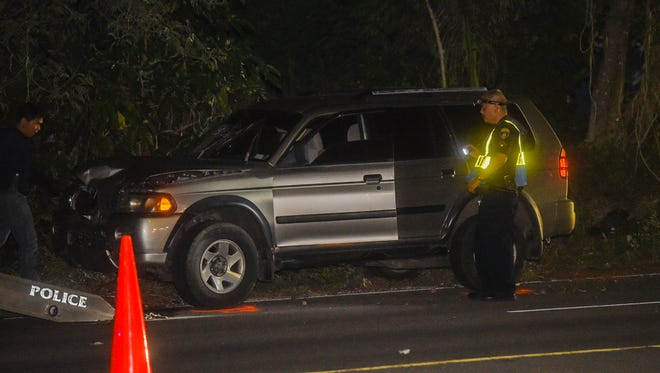 A Guam Police Department officer investigates a Mitsubishi Montero involved in an auto-pedestrian crash as in Barrigada on June 11, 2017.
