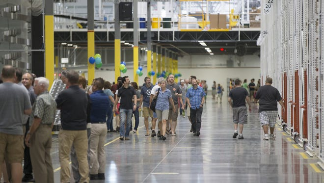 People explore the new distribution floor at REI's Fulfillment Center on July 7, 2016, in Goodyear.