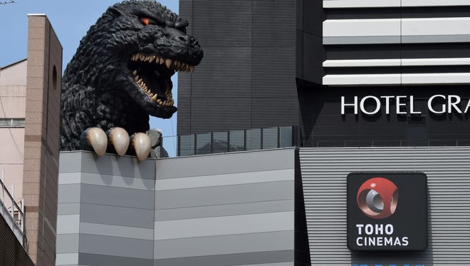 A life-size Godzilla head appears on a balcony of the eighth floor of Hotel Gracery Shinjuku at Kabukicho shopping district in Tokyo on April 9, 2015.