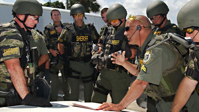 Sgt. Dennis Casey, team leader of the Brevard County Sheriff's Office SWAT team, briefs his squad before a joint tactical operation.