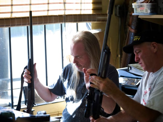 Travis Esarey (left) and Mike Howland inspect a couple of shotguns at E & E Sporting Goods. Esarey has worked at the shop off-and-on ever since he was a kid. Howland is one of the business's regulars.