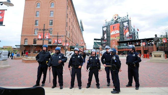Baltimore police officers stand outside the stadium prior to the cancellation of the game between the Chicago White Sox and Baltimore Orioles at Oriole Park at Camden Yards.