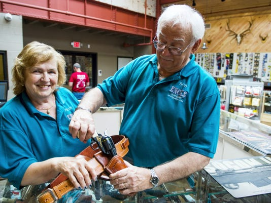 Fran and Bob Enck, owners of Enck's Gun Barn, pose with a cowboy action pistol and holster at their new location at 17 E. Main Ave., Myerstown, on Tuesday
