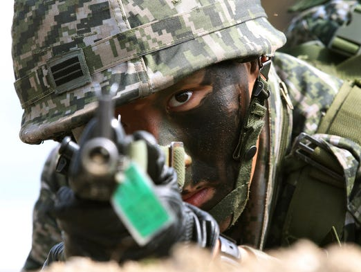 A South Korean marine aims his rifle during a joint landing exercise with U.S. forces on March 31 in Pohang, South Korea.  South Korea returned fire into North Korean waters after artillery shells from a North Korean military drill fell into the waters of a disputed western sea boundary.