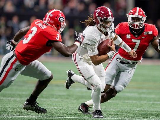 Alabama quarterback Jalen Hurts (2) gets by Georgia inside linebacker Roquan Smith (3) and outside linebacker Lorenzo Carter (7) in first half action of the College Football Playoff National Championship Game in the Mercedes Benz Stadium in Atlanta, Ga., on Monday January 8, 2018.