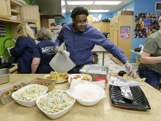 FILE - Painting Pathways Clubhouse member Al Betts lays out a variety of food he helped prepare during lunch April 26, 2018.