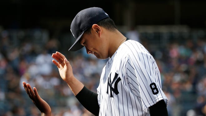 New York Yankees starting pitcher Masahiro Tanaka is greeted at the dugout steps after manager Joe Girardi took him out during the seventh inning of the Yankees' 5-3 victory over the Toronto Blue Jays in a baseball game in New York, Monday, Sept. 5, 2016.