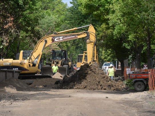 Construction crews work on Villa Avenue installing