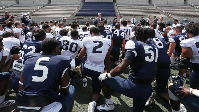 University President Gary L. Miller addresses the football team at InfoCision Stadium during a campus tour after Miller was named president in August.