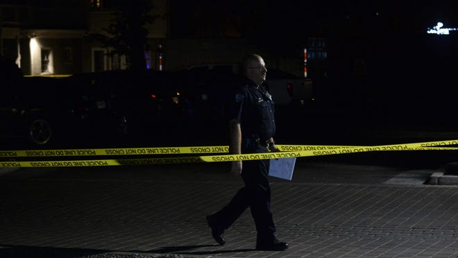 An officer walks through the scene of a fatal shooting near Laurel Street and College Avenue on Tuesday.