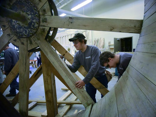 Jordan Murray, left, and Brandon Gordon work on the Chambersburg water wheel in carpentry class Wednesday, Dec. 16, 2015 at Franklin County Career and Technology School.