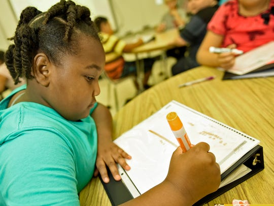Student Nyasia Singleton works on a math project in her fourth-grade class on Wednesday, September 14, 2016 at Stevens Elementary School. Student scores at the school have shown an increase.