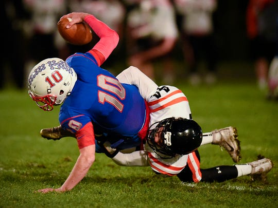 St. Cloud Apollo quarterback Joey Atkinson is sacked for a loss by St. Cloud Tech linebacker Max Martig during the first half Friday at MIchie Field.