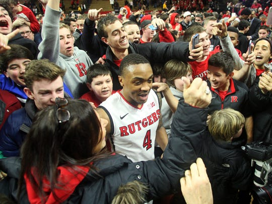 Rutgers' Myles Mack is swarmed by fans after the Scarlet