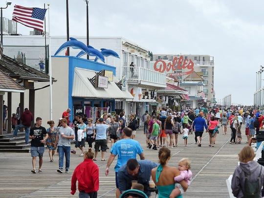 Visitors walk the Rehoboth Beach Boardwalk last month.
