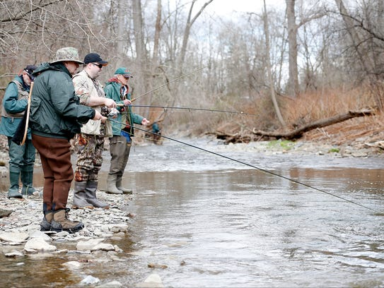 Eager anglers looking for trout cast their line into