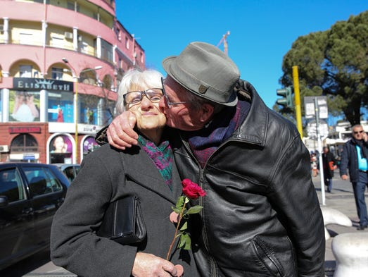 A man kisses his wife after giving her a rose on Valentine's