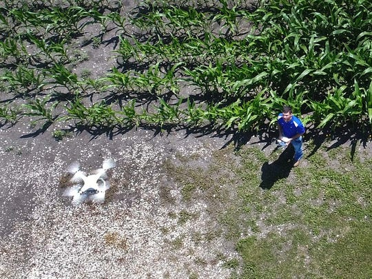 Andrew Lauver certified services agent with DuPont Pioneer flies his DJI Phantom III to check crops Wednesday, July 5, 2017 near Ralston, Iowa.