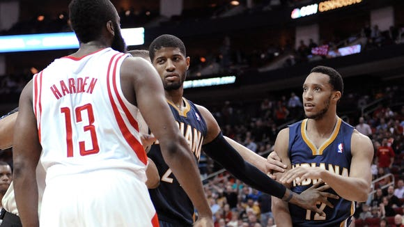 Indiana Pacers' Paul George (24) steps between Houston Rockets' James Harden (13) and Pacers' Evan Turner (12) in the second half of an NBA basketball game Friday, March 7, 2014, in Houston. (AP Photo/Pat Sullivan)