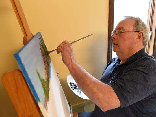 Johnstown artist Mark Nelson paints a forested mountain
