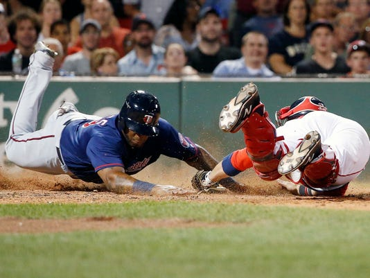 Boston Red Sox's Sandy Leon, right, fails to put the tag on Minnesota Twins' Kennys Vargas at home plate on an RBI-single by Eddie Rosario during the seventh inning of a baseball game in Boston, Saturday, July 23, 2016. (AP Photo/Michael Dwyer)