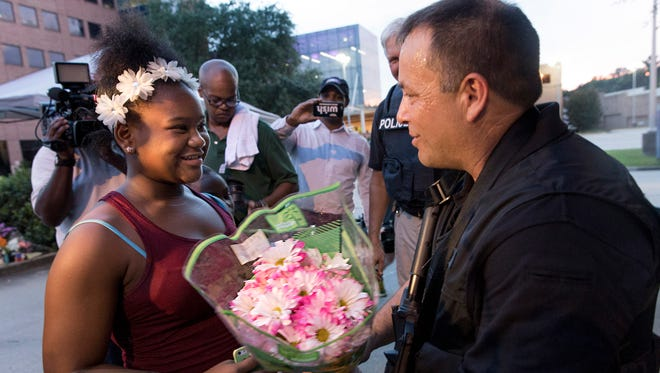 11-year-old Kaylah Reed gives a bouquet of flowers to a policeman standing guard at Our Lady of the Lakes Hospital, in the evening after a shootout left three officers dead in Baton Rouge July 17, 2016.