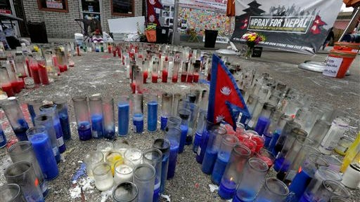 A Nepalese flag stands among candles in Diversity Plaza, in the Jackson Heights neighborhood, of the Queens borough of New York, Thursday. In New York, home to the nation's largest Nepalese community, volunteers from the Hyolmo Youth Club collect money, clothing and food donations to send to the earthquake stricken nation.