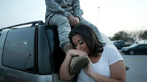 Lucy Hamlin leans on her husband's foot, Specialist Timothy Hamlin, as they wait to be allowed back onto Fort Hood, Texas, where they reside on Wednesday, April 2, 2014. A shooting occurred on the base with at least four dead and 14 injured according to the officials.