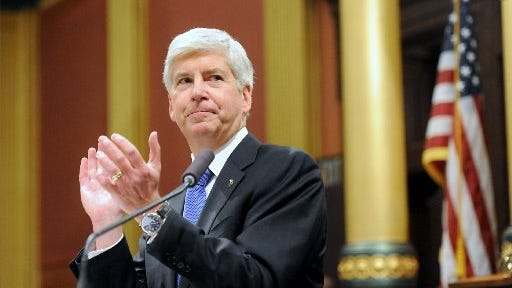 Michigan Gov. Rick Snyder applauds members of the military as he speaks during his State of the State address on the floor of the House at the Capitol in Lansing on Tuesday, Jan. 20, 2015.