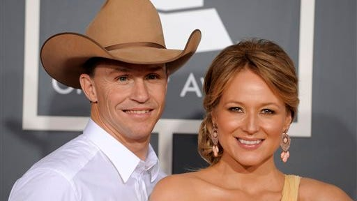 This file photo shows Jewel, right, and her husband Ty Murray at the 53rd annual Grammy Awards in Los Angeles. Jewel and her husband are divorcing after a 16-year relationship. The 40-year-old singer wrote in a letter posted on her website Wednesday, July 2, 2014, that she and Ty Burrell want their separation ?to be nothing less loving than the way we came together.? Jewel and Burrell were married in 2008. They have a son named Kase.