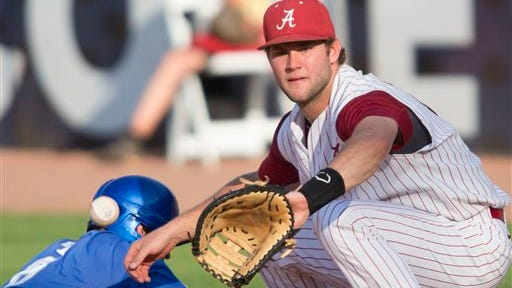 Alabama's Austen Smith can't get the ball in time to tag Kentucky's Matt Reida  at first on a pick off play during the Southeastern Conference NCAA college baseball tournament on Tuesday, May 20, 2014, in Hoover, Ala. (AP Photo/Hal Yeager)