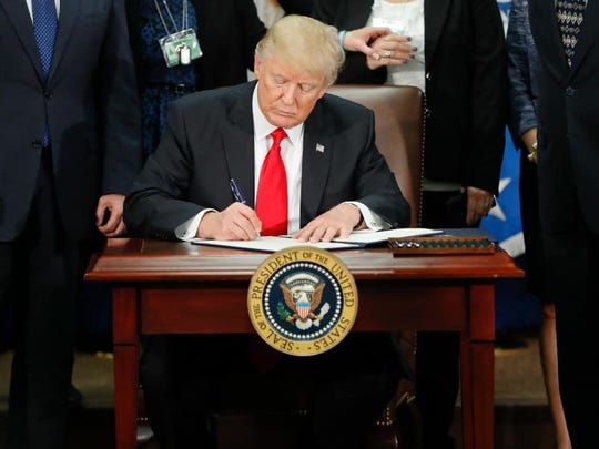 President Donald Trump signs an executive order for border security and immigration enforcement improvements at the Department of Homeland Security in Washington, D.C.