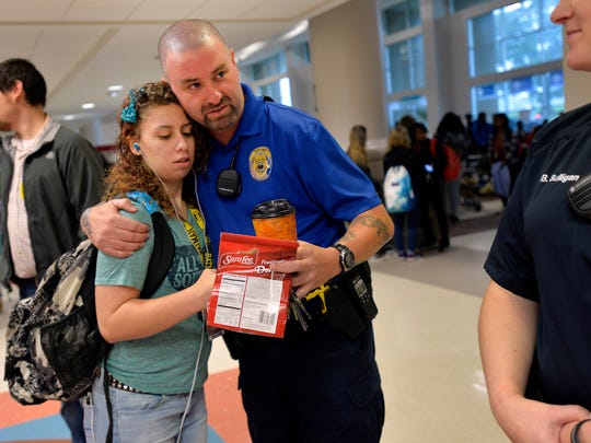A student gives Tony Koutsos, a school resource officer at Mauldin High School, a hug before classes start on Nov. 6, 2015.
