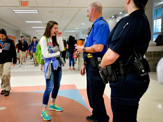 A student gives Tony Koutsos, a school resource officer at Mauldin High School, a bag of doughnuts before classes start on Nov. 6, 2015.