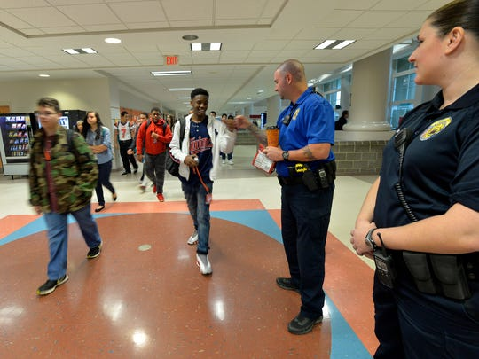 A student gives Tony Koutsos, a school resource officer at Mauldin High School, a fist bump before classes start on Nov. 6, 2015.