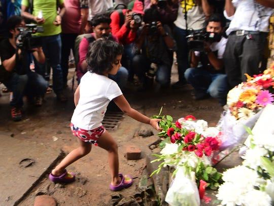 A Bangladeshi child leaves a floral arrangement on