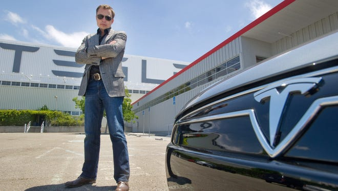 Elon Musk, CEO of Tesla Motors, with a Model S electric car outside the Tesla factory in Fremont, Calif.