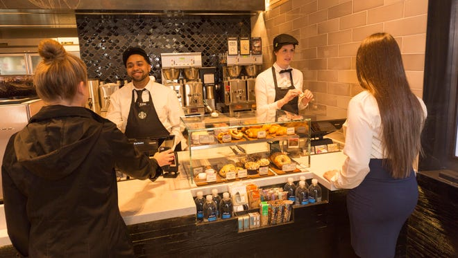 Customers at the Starbucks Express store in Manhattan. Starbucks reported third-quarter results Thursday.