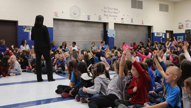 Washington Elementary School students listen to state politicians and Utah Educational Savings Account officials during an assembly about saving for college on Dec. 16, 2016.