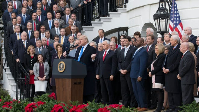 President Trump and GOP lawmakers celebrate passage of the sweeping Republican overhaul of the tax code at a Dec. 20 White House event.