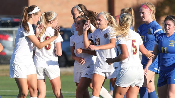 Arlington's Molly Feighan, center, celebrates with