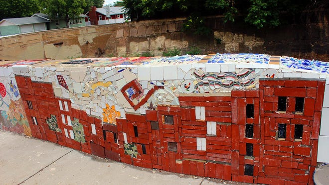 Historic brick buildings, a kite and sun highlight this section of the mosaic wall in Florence.
