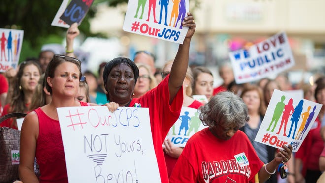 Teachers and others opposed to the Kentucky state government's takeover of Jefferson County's public school system protest Tuesday evening outside the VanHoose Building on Newburg Road. May 29, 2018