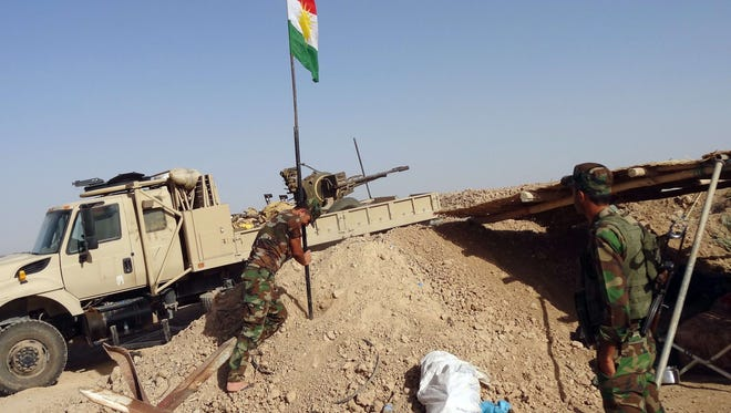 """Kurdish Peshmerga forces raise the Kurdish flag at a checkpoint on the road leading from Kirkuk to northern Iraqi city of Tikrit on June 30, 2014. Jihadists spearheading a Sunni militant offensive in Iraq have declared an """"Islamic caliphate"""" and ordered Muslims worldwide to pledge allegiance to their chief, in a bid to extend their authority."""