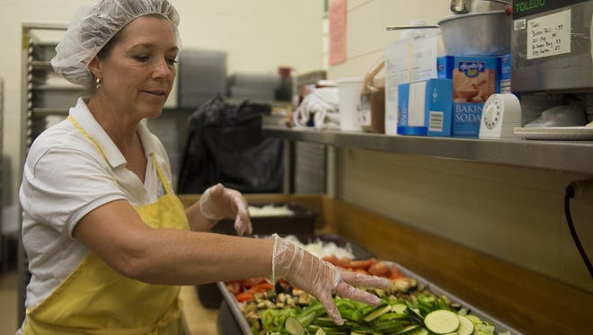Oshkosh Area School District Food Services Director Peggy West prepares cut vegetables to be seasoned for the ratatouille that was prepared from more than a ton of vegetables for the Green Bay and Oshkosh school districts Tuesday.