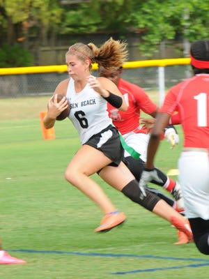 Jensen Beach High School's Josephine Debiase pulls away from Miami Edison defenders in Friday's FHSAA State Flag Football Championships semifinal at Citizens Park in Gainesville.